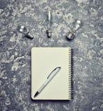Libreta del inconformista, pluma y bulbo incandescente en una tabla concreta Fotos de archivo