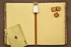 Libreta del vintage, tarro con algo blanco, naipe y dados Fotografía de archivo