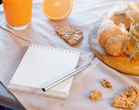 Libreta en blanco cerca de la galleta del cruasán y de la avena Planeamiento sano del desayuno y de la mañana foto de archivo libre de regalías