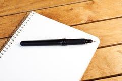 Libreta en blanco con la pluma negra Imagen de archivo libre de regalías