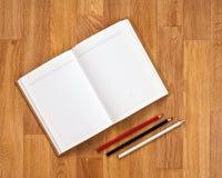 Libreta en blanco con los materiales de oficina en la tabla de madera imagen de archivo