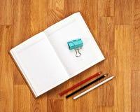 Libreta en blanco con los materiales de oficina en la tabla de madera fotos de archivo