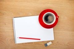 Libreta en blanco con los materiales de oficina y la taza de café roja Imagen de archivo