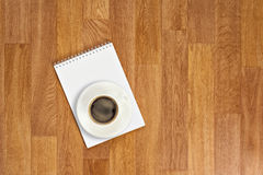 Libreta en blanco con los materiales de oficina y taza de café en t de madera imagenes de archivo