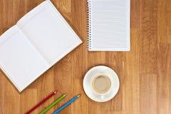 Libreta en blanco con los materiales de oficina y taza de café en t de madera fotografía de archivo libre de regalías