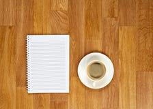 Libreta en blanco con los materiales de oficina y taza de café en t de madera Fotos de archivo libres de regalías