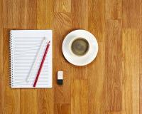 Libreta en blanco con los materiales de oficina y taza de café en t de madera imagen de archivo libre de regalías