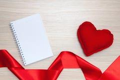 Libreta en blanco, corazón y cinta formada en la tabla de madera Foto de archivo libre de regalías