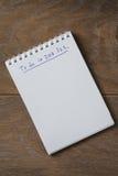 Libreta en blanco en la tabla de madera con la frase a hacer en 2017 Foto de archivo libre de regalías