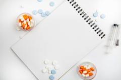 Libreta en blanco entre diversas medicaciones en un fondo blanco, plantilla para el texto fotografía de archivo