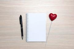 Libreta en blanco, lápiz y corazón rojo en la tabla de madera Imagenes de archivo