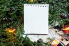 Libreta en blanco en ramas de árbol de navidad, la decoración del Año Nuevo y la guirnalda imágenes de archivo libres de regalías