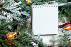 Libreta en blanco en ramas de árbol de navidad, la decoración del Año Nuevo y la guirnalda foto de archivo libre de regalías