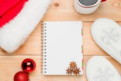 libreta en la primavera, bolas de la Navidad y un casquillo de Papá Noel Imágenes de archivo libres de regalías