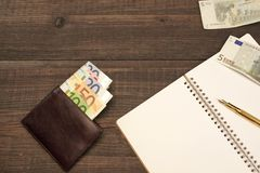 Libreta espiral abierta, cartera con el efectivo euro, Pen On Wood Fotos de archivo