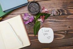 Libreta, flores y fregar en una tabla de madera Nota fotos de archivo