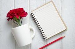 Libreta, lápiz y flores del clavel Foto de archivo libre de regalías