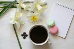 Libreta, macarons, taza de café y narcisos en una tabla blanca Lugar de trabajo inspirado fotografía de archivo libre de regalías