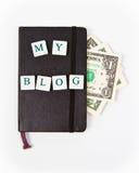 Libreta negra con mi mensaje y dólares del blog Fotos de archivo