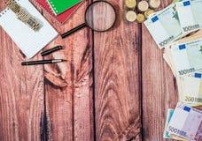 libreta, pluma, calculadora con la moneda euro y billetes de banco en el escritorio Fotografía de archivo