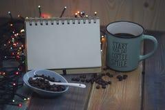 Libreta, taza azul y granos de café en un bowln Imagen de archivo libre de regalías