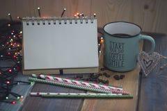 Libreta, taza azul y palillos dulces en un tablenn de madera Fotografía de archivo