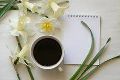 Libreta, taza de café y narcisos en una tabla blanca Lugar de trabajo inspirado fotografía de archivo