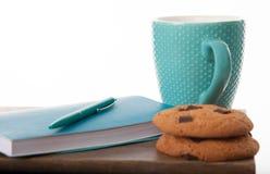 Libreta, taza, pluma en color de la turquesa con las galletas de microprocesador de chocolate Tabla de madera y fondo blanco Gran Fotografía de archivo libre de regalías