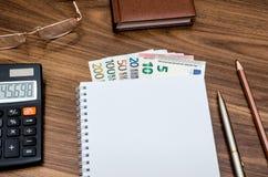 Libreta vacía con el dinero, el móvil, la calculadora y la pluma euro Foto de archivo