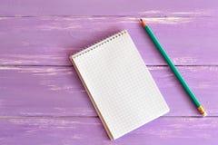 Libreta y lápiz en blanco en el tablero de madera Imagen de archivo libre de regalías