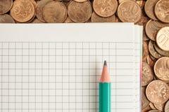 Libreta y lápiz en monedas Fotografía de archivo libre de regalías