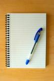Libreta y pluma en el escritorio de madera Fotografía de archivo libre de regalías