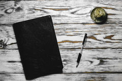 Libreta y pluma en una tabla blanca Fotos de archivo