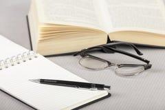 Libreta y pluma en una tabla con un libro Fotografía de archivo libre de regalías