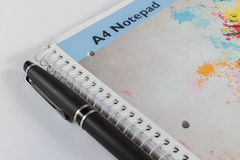 Libreta A4 y pluma negra en el fondo blanco Fotos de archivo libres de regalías
