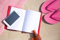 Libreta y teléfono elegante en fondo de la playa arenosa Fotografía de archivo libre de regalías