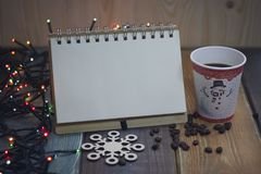 Libreta y vidrio en una tabla de madera de la Navidad y un snowflaken Imagenes de archivo