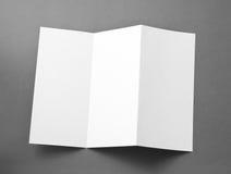 Libretto piegante in bianco della pagina su fondo grigio. Fotografie Stock