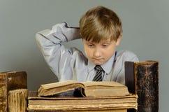 Libri antichi un ragazzo, un bambino prodigio Fotografia Stock Libera da Diritti