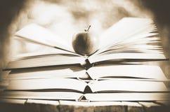 Libri aperti con la mela su storia di inverno Immagine Stock