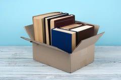 Libri aperti sopra sulla tavola di legno della piattaforma e sul fondo blu Di nuovo al banco Concetto di istruzione con lo spazio Fotografia Stock