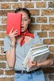 Libri asiatici alla moda della tenuta della ragazza con espressione facciale Fotografia Stock Libera da Diritti