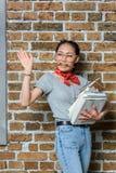 Libri asiatici della tenuta della donna con il gesto di mano Fotografia Stock