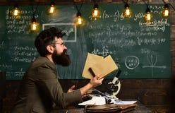 Libri barbuti della tenuta dell'uomo in università Ricerca dello scienziato con il microscopio Uomo con la barba e baffi sulla la Immagini Stock Libere da Diritti