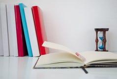 Libri, clessidre e taccuino aperto sulla tavola bianca Fotografia Stock
