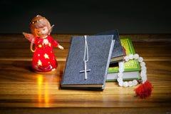 Libri cristiani con un incrocio, le perle e una figura di un angelo Immagini Stock