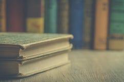 Libri d'annata su uno scaffale per libri di legno con i libri nel fondo Immagini Stock