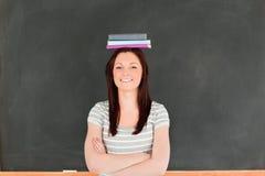 Libri da portare della donna sveglia di Smilling sulla sua testa Fotografie Stock Libere da Diritti