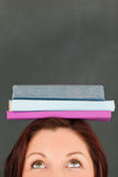Libri da portare felici della giovane donna sulla sua testa Fotografie Stock Libere da Diritti