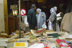 Libri da vendere al mercato delle pulci, alla donna musulmana ed all'uomo nel fondo, Parigi, Francia immagini stock